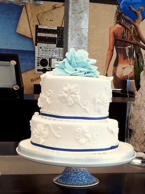 2 Laags witte bruidstaart met blauwe linten en licht blauwe roos