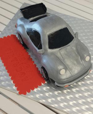 Een zilvere verjaardagstaart in de vorm van een auto