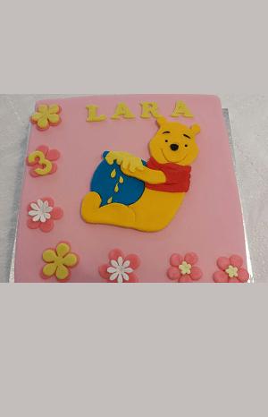 Roze verjaardagstaart met een tekening van winnie de pooh