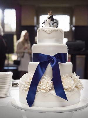 5 Laags witte bruidstaart met blauwe lint, witte rozen en een bruidspaar