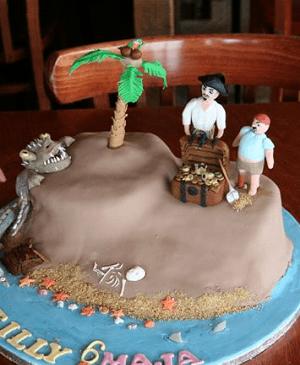 Verjaardagstaart in de vorm van een eiland met piraten en een schat
