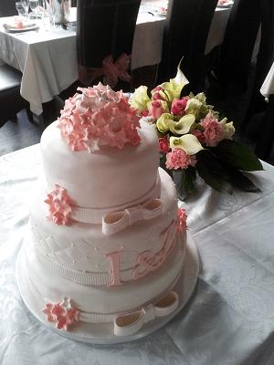 Witte bruidstaart met roze letters en roosjes