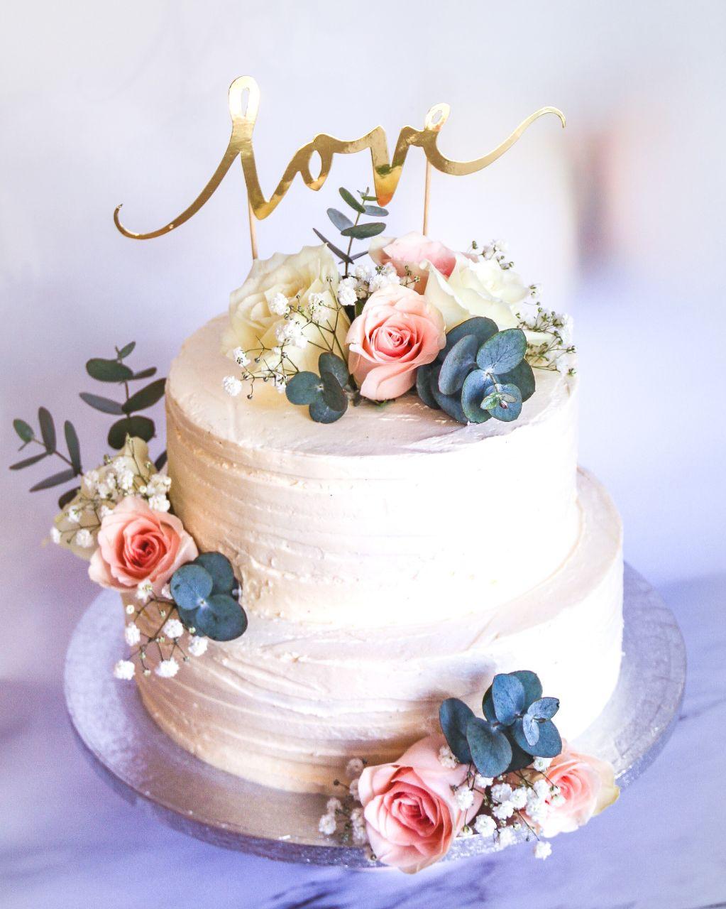 witte-structuur-streepjes-botercrème-taart-met-zacht-roze-bloemen-en-goud-love-taart-topper