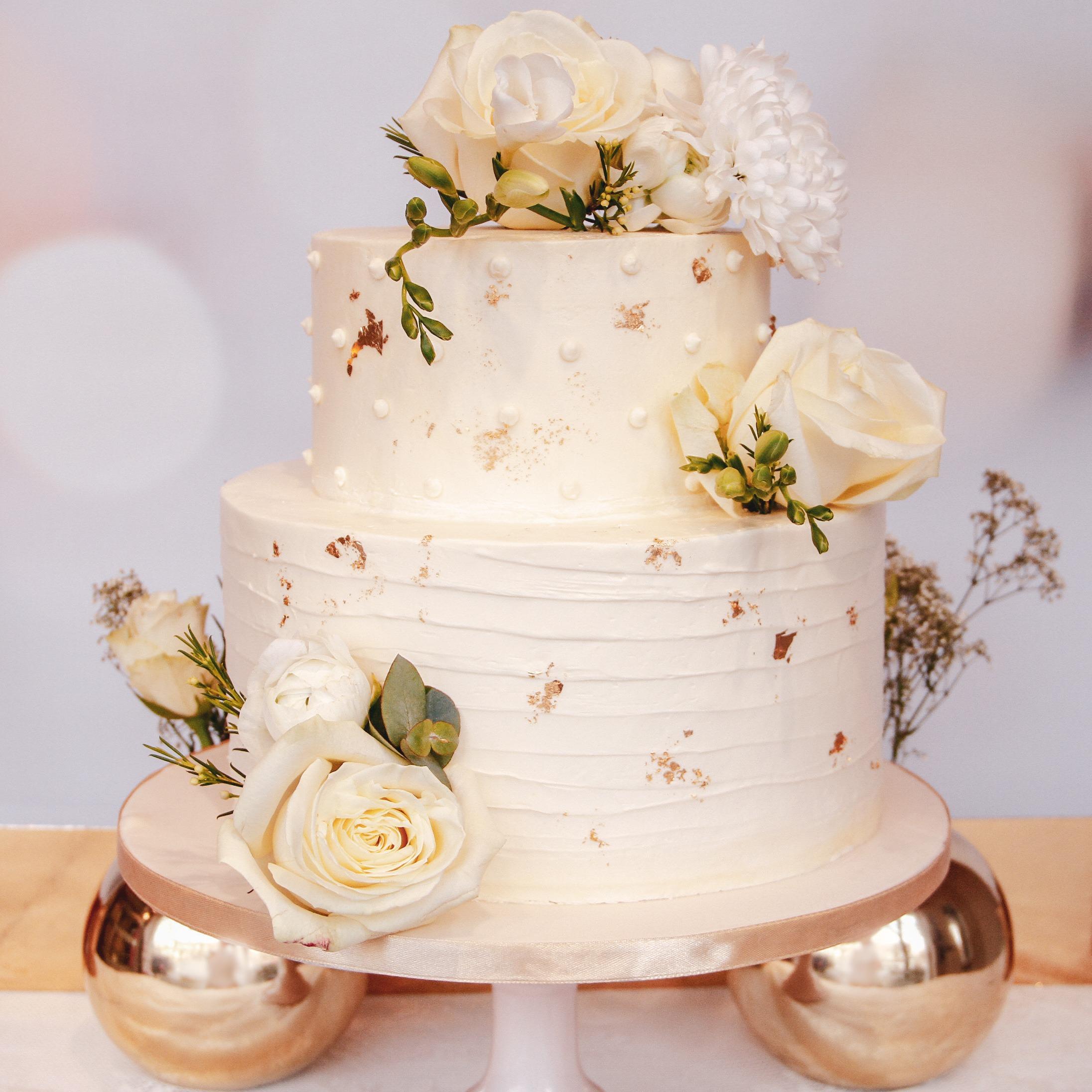 witte-botercrème-afgsemeerde-bruidstaart-met-witte-rozen-en-goud-blad
