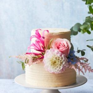 witte bruidstaart met twee lagen en bloemen in het roze en wit