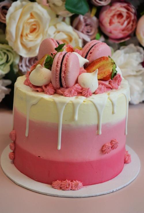 roze-lichtroze-wit-laagjes-taart-met-witte-drip-roze-macarons-aardbeien-en-meringue